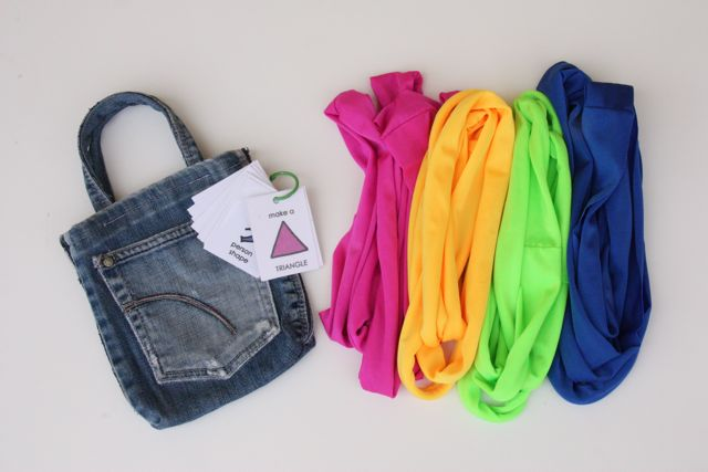 Handmade jean pocket bag and activity cards laying besides pink, yellow, green and blue shape stretchies.