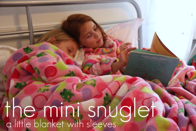 Two little girls resting under the mini snuglet a little blanket with sleeves.